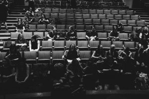 Women sitting in an audience prepping for the choir event